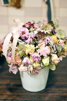 Primer plano de un jarrón con flores marchitas sobre una mesa de madera
