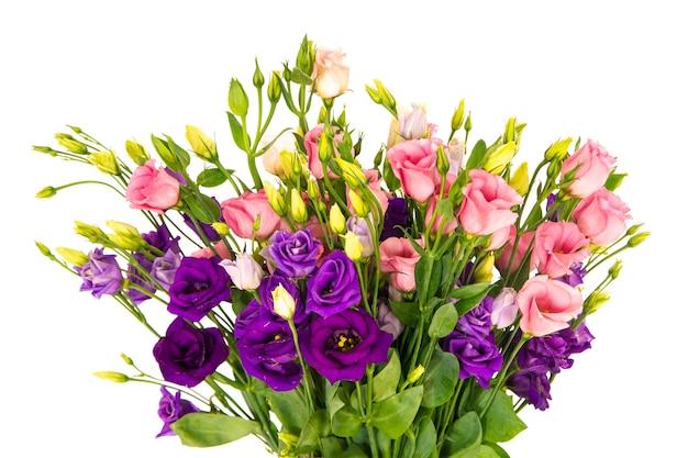Primer plano de un jarrón lleno de hermosas rosas rosadas y flores púrpuras con un fondo blanco.