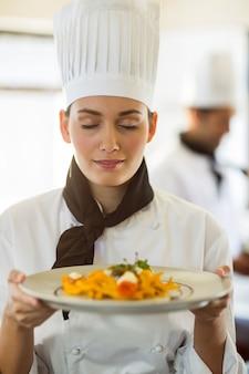 Primer plano del jefe de cocina con los ojos cerrados oliendo comida