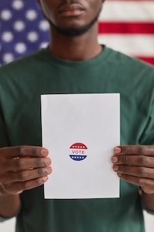 Primer plano de un joven africano que muestra la papeleta durante las elecciones de pie contra la bandera americana