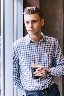 Primer plano de un joven apuesto sosteniendo los vasos de cerveza mirando a cámara