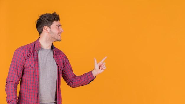 Primer plano de un joven apuntando con su dedo algo contra un fondo naranja