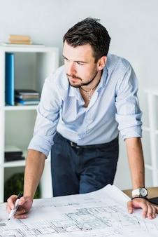 Primer plano de un joven arquitecto masculino con blueprint en el escritorio