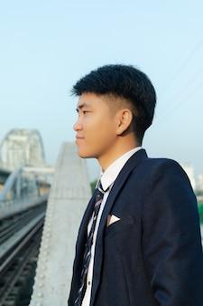 Primer plano de un joven asiático con un traje de pie sobre un puente y mirando a otro lado