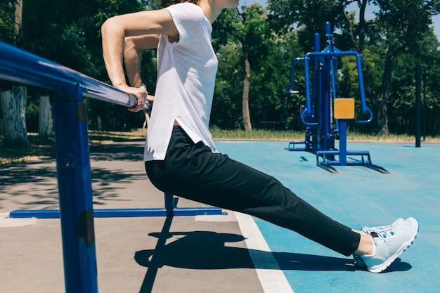 Primer plano de una joven atlética haciendo ejercicios para los tríceps en el patio de recreo en el verano