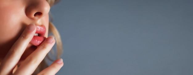 Primer plano joven bastante rubia con el dedo en los labios coquetea mirar contra el fondo azul oscuro del aislamiento. emoción femenina feliz y actriz de maestro. concepto de inspiración de satisfacción. copia espacio