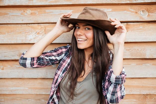 Primer plano de una joven y bella mujer feliz vaquera con sombrero sobre fondo de madera