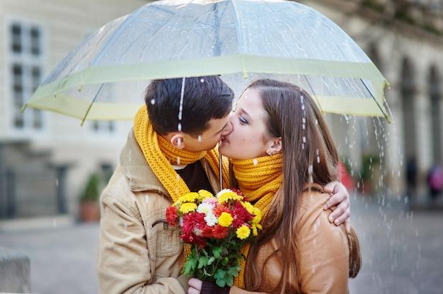 Primer plano de la joven y bella pareja besándose bajo el paraguas
