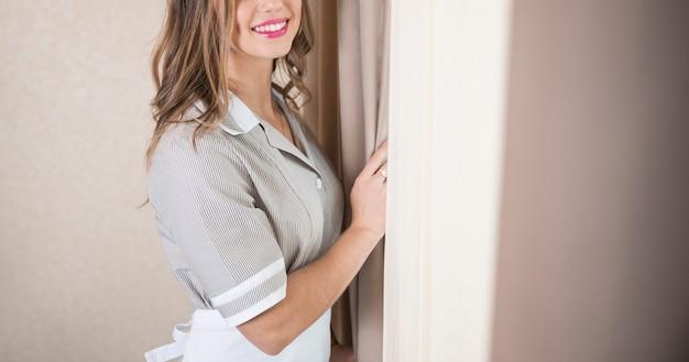 Primer plano de la joven camarera femenina de pie cerca de la cortina