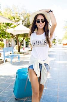 Primer plano de joven delgada caminando en un parque con maleta azul detrás de ella. lleva pantalones cortos de mezclilla, camiseta blanca, sombrero de paja y gafas de sol oscuras. ella sonríe y sostiene su sombrero con una mano