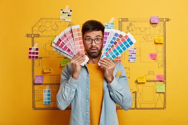 Primer plano del joven diseñador preparándose para renovar junto al boceto del plan maestro de la casa