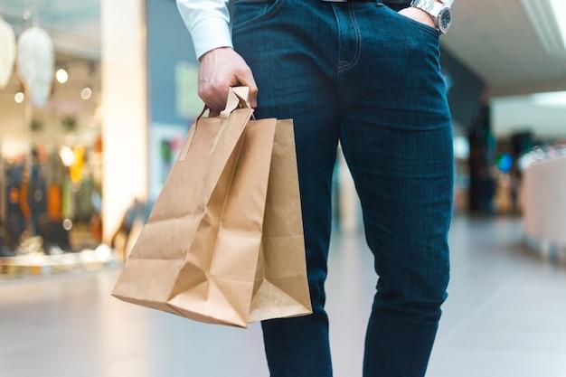 Primer plano de un joven elegante caminando en un centro comercial con bolsas de compras amigables con la ecología en la mano con productos y ropa. ventas, concepto de descuento agotado. venta de temporada.