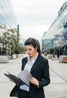 Primer plano de una joven empresaria leyendo la carpeta al aire libre