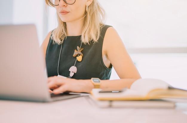Primer plano de joven empresaria usando laptop con diario en lugar de trabajo