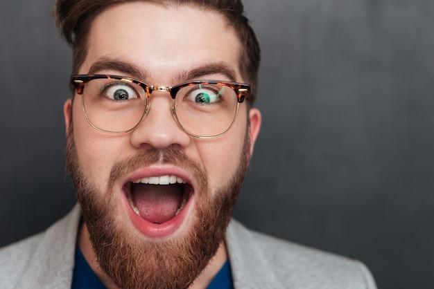 Primer plano de un joven empresario feliz sorprendido en vasos con la boca abierta