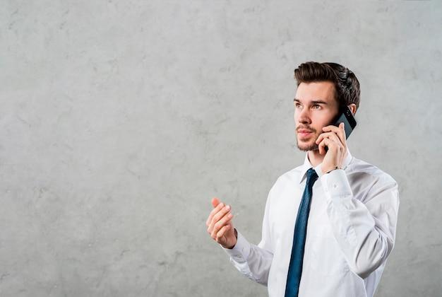 Primer plano de un joven empresario hablando por teléfono inteligente que mira de lejos contra un muro de hormigón gris