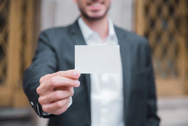 Primer plano de un joven empresario que muestra la tarjeta de visita blanca frente a la cámara