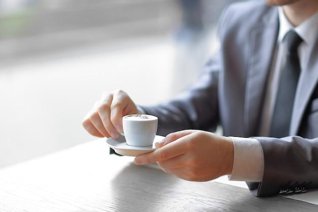 Primer plano de un joven empresario con una taza de café en la mano comprueba algunos gráficos.
