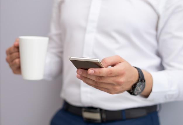Primer plano de joven empresario mediante teléfono móvil en el interior