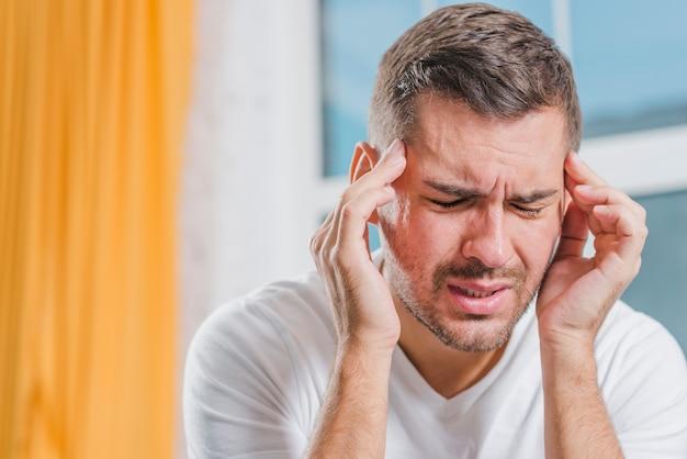 Primer plano de un joven haciendo muecas de dolor al tocar su cabeza con los dedos