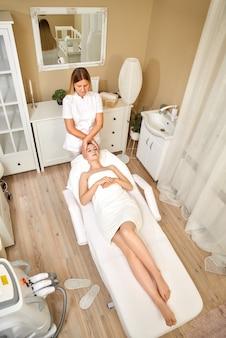 Primer plano de joven masajista haciendo masaje en la cara para joven cliente bastante femenina en el salón de spa. vista superior
