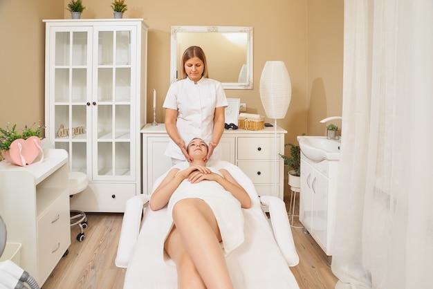Primer plano de joven masajista haciendo masaje en la cara para joven cliente bastante femenino en el salón de spa