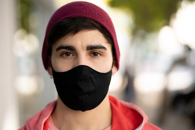 Primer plano de un joven con una máscara protectora mientras está de pie al aire libre en la calle. concepto urbano. nuevo concepto de estilo de vida normal.