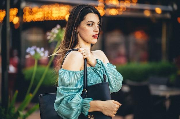 Primer plano de una joven mujer europea en una blusa turquesa
