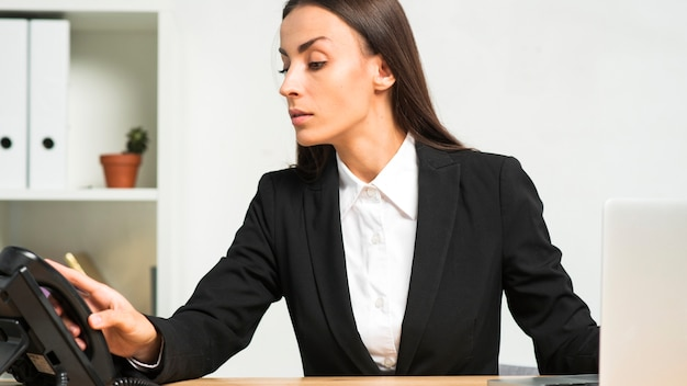 Primer plano de una joven mujer sosteniendo teléfono receptor en la oficina