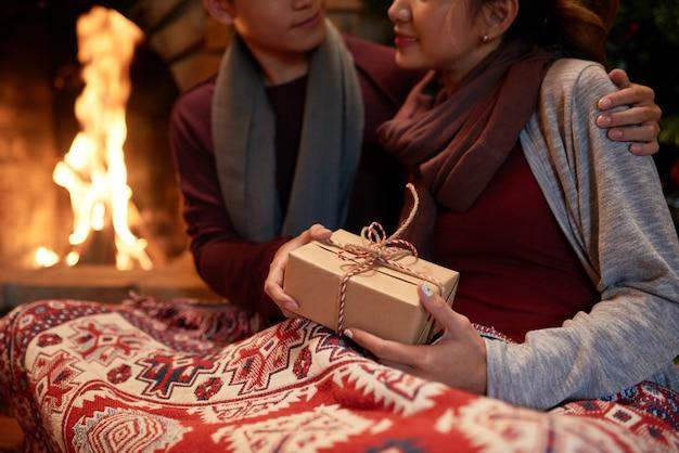 Primer plano de una joven pareja abrazados a la chimenea con un regalo en manos femeninas