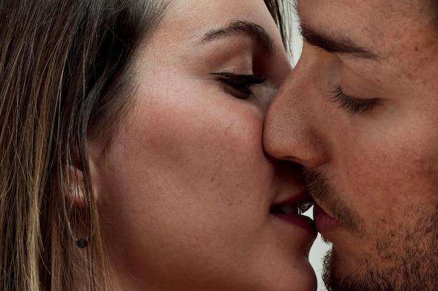 Primer plano joven pareja besándose