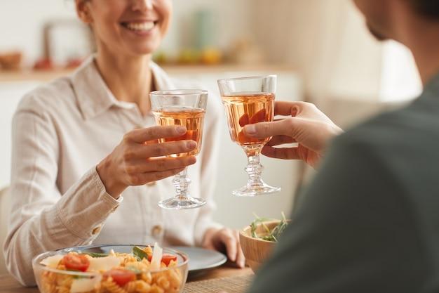 Primer plano de la joven pareja cenando juntos en la mesa y brindando con copas de vino