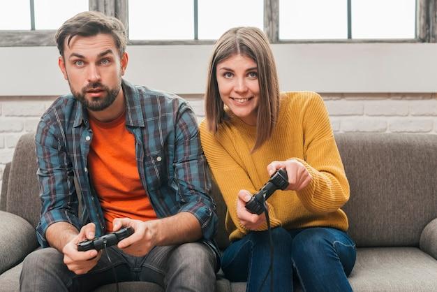 Primer plano de la joven pareja jugando al videojuego con joystick