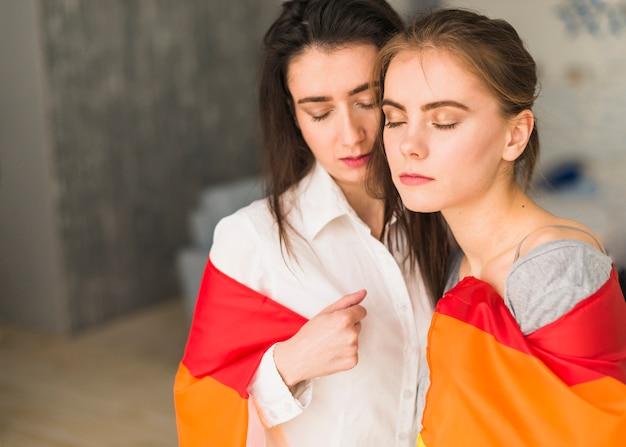 Primer plano de una joven pareja de lesbianas que se envuelve en una bandera de arco iris que cierra sus ojos