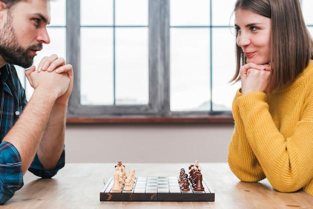 Primer plano de la joven pareja con la mano entrelazada mirando el uno al otro jugando al ajedrez