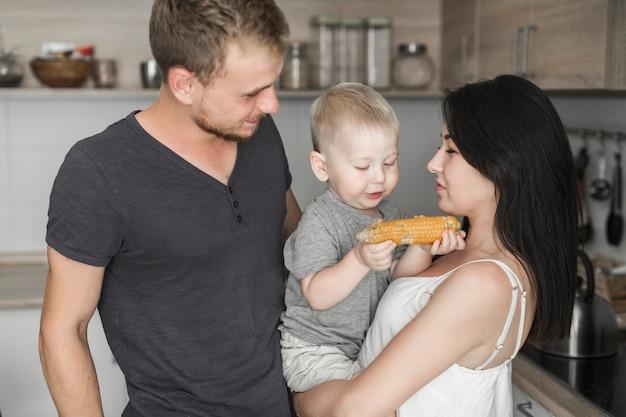 Primer plano de la joven pareja mirando a su hijo comiendo maíz