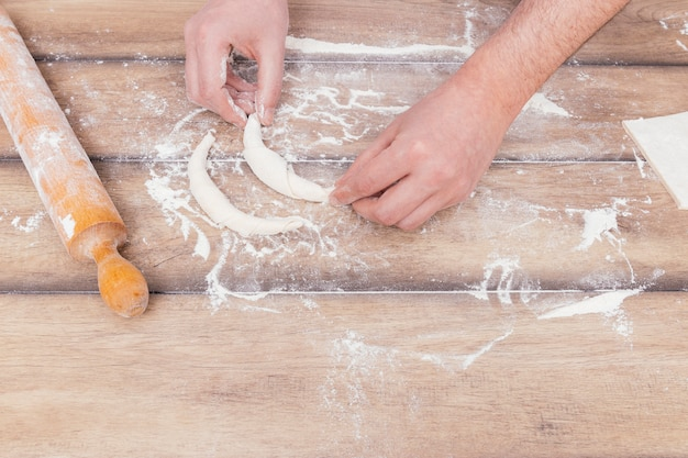 Primer plano de joven pastelero que hace un poco de croissant en la mesa