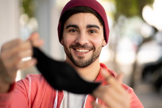 Primer plano de un joven poniéndose mascarilla mientras está de pie al aire libre en la calle. concepto urbano. nuevo concepto de estilo de vida normal.
