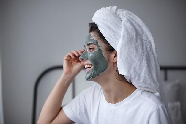 Primer plano de joven riendo atractiva mujer de pelo oscuro en camiseta blanca con máscara cosmética de arcilla azul en su rostro mirando felizmente a un lado y tocando suavemente su ojo. rutina de cuidado de la piel por la mañana