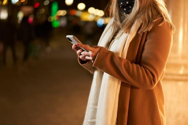 Primer plano de una joven rubia frente a un escaparate con un teléfono inteligente, escribiendo un mensaje, en una ciudad de noche, con luz de fondo.