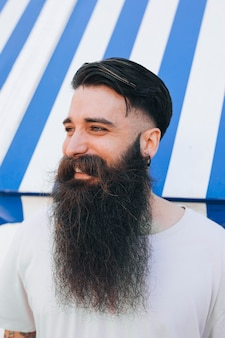 Primer plano de un joven sonriente con su larga barba
