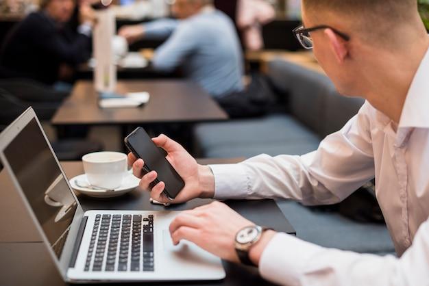 Primer plano de un joven sosteniendo un móvil en la mano usando una tableta digital en una cafetería