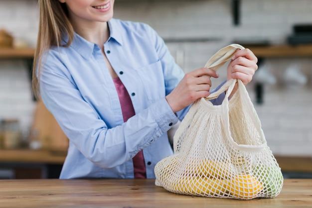 Primer plano joven sosteniendo reutilizable con frutas