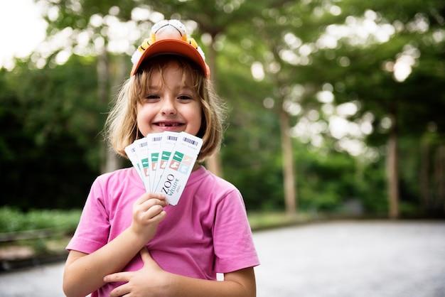 Primer plano de jovencita caucásica mostrando entradas para el zoológico