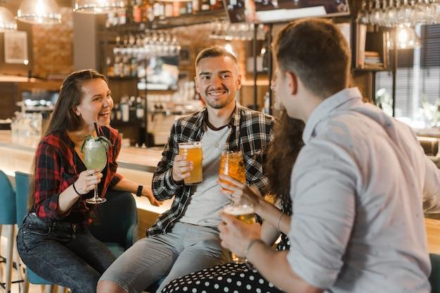 Primer plano de jóvenes amigos disfrutando de bebidas por la noche en la discoteca