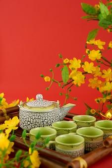 Primer plano de juego de té servido sobre fondo rojo y flores.