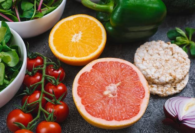 Primer plano de jugosas frutas cítricas a la mitad con verduras y pastel de arroz inflado