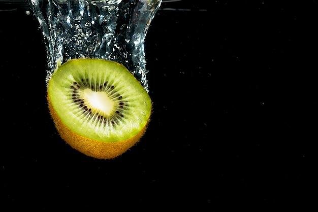 Primer plano de kiwi reducido a la mitad que cae con salpicaduras de agua