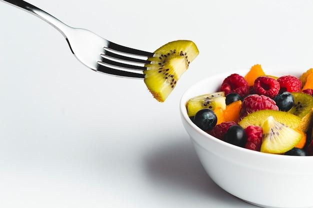 Primer plano de kiwi en un tenedor con un tazón de fruta