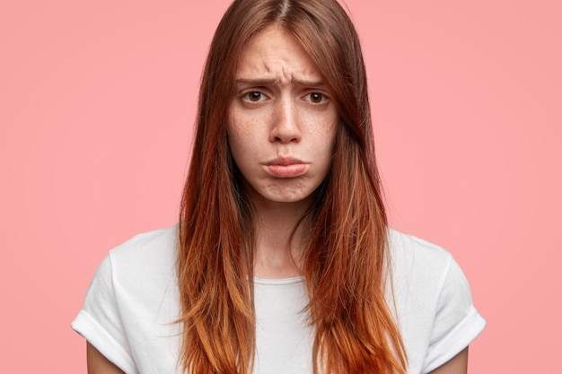 Primer plano de los labios femeninos hoscos y guapos, tiene expresión triste, aislada sobre fondo rosa.